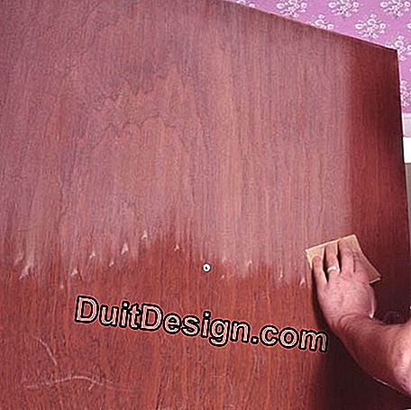 Sanding the damaged varnish of the door